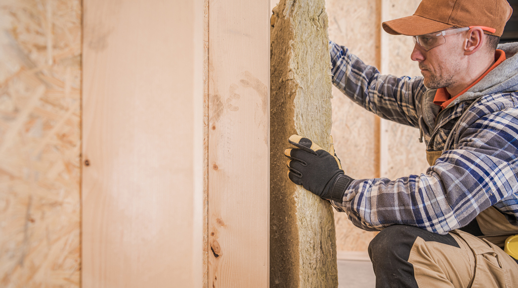 Worker Insulating House Walls with Piece of Mineral Wool
